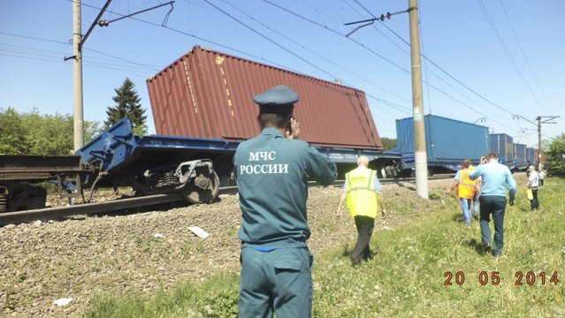 An Emergencies Ministry member speaks on a phone in front of a freight train after a collision with a passenger train in Moscow region in this May 20, 2014 picture provided by the Russian Emergencies Ministry. A passenger train on its way to Moldova collided with a freight train near Moscow on Tuesday, killing at least four people and injuring 15, a spokeswoman for Russia's Emergencies Ministry said. (Photo by Reuters/Press Service of Russian Emergencies Ministry of Moscow Region)