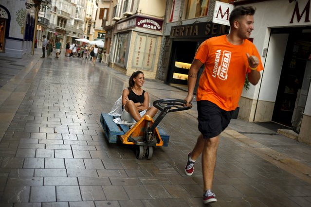 A worker runs as he pulls a cart with a woman along a street in downtown Malaga, southern Spain, July 23, 2015. Spain's jobless rate dropped to its lowest level in over three years in the second quarter, offering a boost to Rajoy as he seeks to persuade voters that an economic recovery is taking root. At 22.4 percent, the unemployment rate is still higher than anywhere else in Europe bar crisis-hit Greece and has not dipped below a fifth of the workforce in five years, even after Spain exited recession in mid-2013. (Photo by Jon Nazca/Reuters)