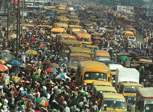 Commuters and traders of the Oshodi area of Lagos, the commercial nerve centre of Nigeria with a population of over twelve million people, make their way through crowded streets on April 30, 2001. (Photo by George Esiri/Reuters)