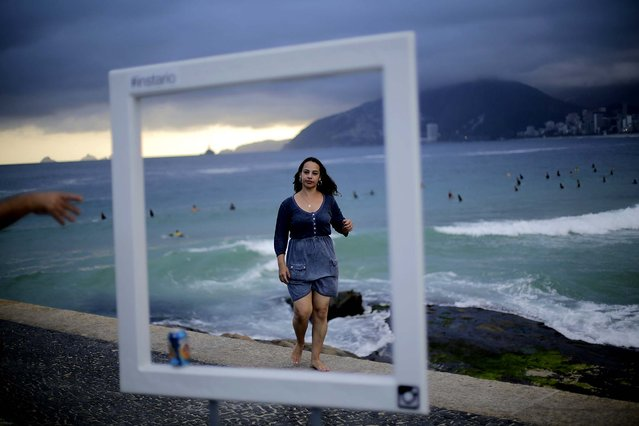 Tourists pose for photos in front of Brazil's famous Ipanema beach in Rio de Janeiro, on June 11, 2014. (Photo by Wong Maye-E/Associated Press)