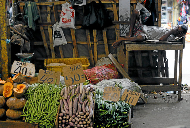 A vendor sleeps at his vegetables shop at a main market in Colombo, Sri Lanka May 31, 2016. (Photo by Dinuka Liyanawatte/Reuters)