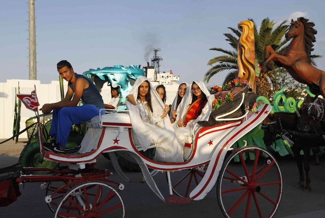 Tunisian girls in traditional Sefsari costumes sit on a horse carriage during the Aoussou Carnival in Sousse, Tunisia July 26, 2015. (Photo by Anis Mili/Reuters)