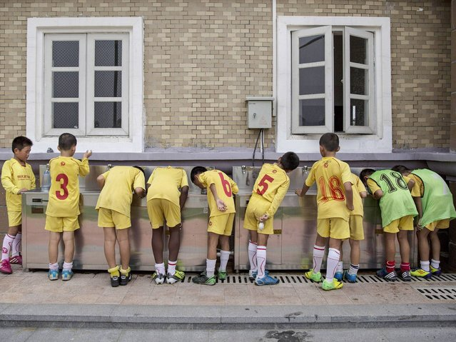 Children drink water from a communal tap after training at the Evergrande International Football School near Qingyuan in Guangdong Province. (Photo by Kevin Frayer/Getty Images)