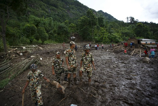 Nepalese army personnel stand on muddy ground during a rescue operation after a landslide at Lumle village in Kaski district July 30, 2015. (Photo by Navesh Chitrakar/Reuters)