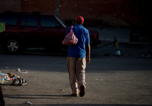 In this May 31, 2016 photo, Julio Noguera leaves the Coche public market after collecting discarded vegetables from the trash area in Caracas, Venezuela. Until recently, Noguera worked at a bakery. But he now spends his evenings searching through the garbage for food. (Photo by Fernando Llano/AP Photo)