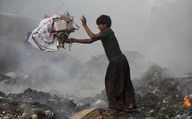 A boy throws a bundle of rubbish while searching for recyclables from the pile of smoldering garbage dump along a street in Karachi, Pakistan, July 31, 2015. (Photo by Akhtar Soomro/Reuters)