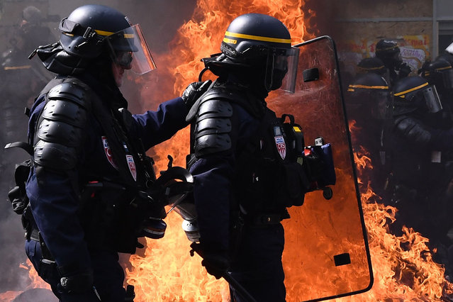 Anti-riot police walk past a buring barricade as they clash with protesters during a May Day demonstration in Paris, on May 1, 2019. Paris riot police fired teargas as they squared off against hardline demonstrators among tens of thousands of May Day protesters, who flooded the city in a test for France's zero-tolerance policy on street violence. (Photo by  Anne-Christine Poujoulat/AFP Photo)