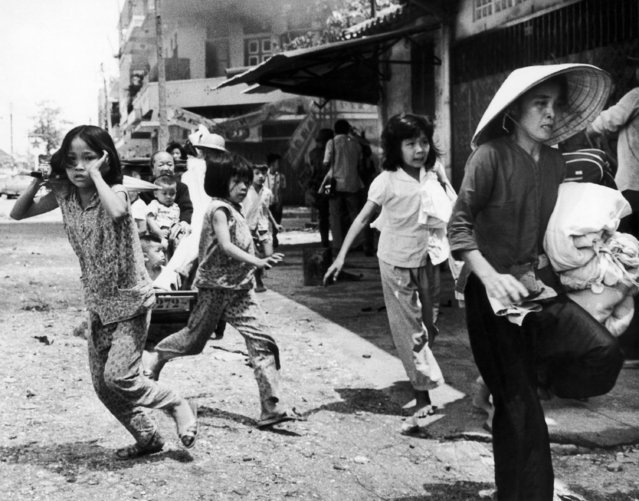Residents rush to leave a threatened section of Cholon, the Chinese quarter of Saigon on June 1, 1968. Vietcong units moved into the area by passing Vietnamese Marines fighting to the west and fired on government troops. Reacting instinctively, residents picked up their personal belongings, abandoned their homes, and fled. (Photo by Eddie Adams/AP Photo)