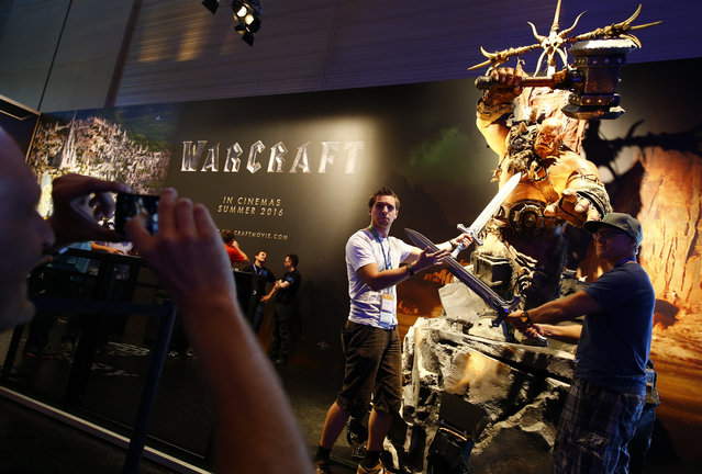 """People pose in front of one of the characters from the """"World of Warcraft"""" game during the Gamescom 2015 fair in Cologne, Germany August 5, 2015. (Photo by Kai Pfaffenbach/Reuters)"""
