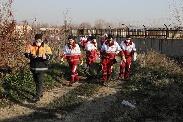 Rescue workers carry the body of a victim of an Ukrainian plane crash in Shahedshahr, southwest of the capital Tehran, Iran, Wednesday, January 8, 2020. A Ukrainian airplane carrying 176 people crashed on Wednesday shortly after takeoff from Tehran's main airport, killing all onboard. (Photo by Ebrahim Noroozi/AP Photo)