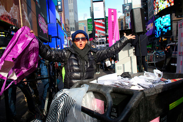 A woman reacts after throwing papers containing hard memories of 2019 in a dumpster during the 13th annual Good Riddance Day in Times Square on December 28, 2019 in New York City. The annual event let people toss, shred, and smash any unpleasant, embarrassing, and unwanted memories from the past year so they can start fresh in 2020. (Photo by Kena Betancur/AFP Photo)
