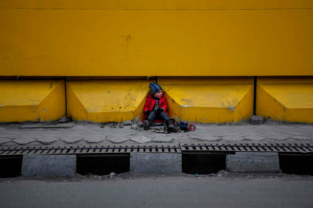 A young shoe-shiner sits as he waits for customers alongside a street in Kabul in December 29, 2019. (Photo by Farshad Usyan/AFP Photo)