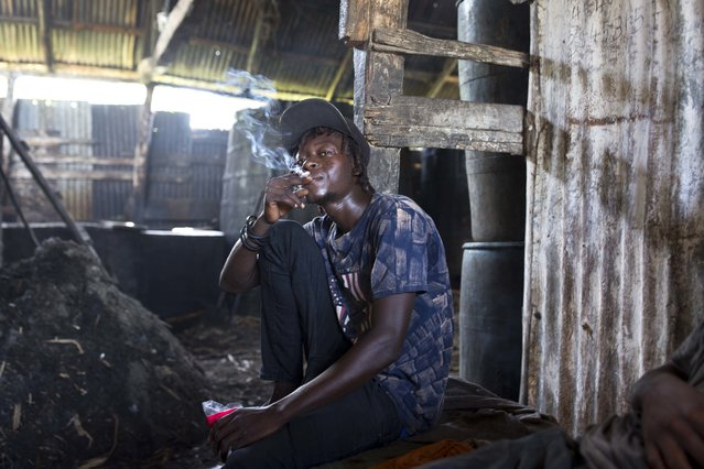 In this June 16, 2017 photo, Beneche Dadou, 20, smokes a cigarette and drinks clairin, a sugar-based alcoholic drink, at the Ti Jean distillery where it's made in Leogane, Haiti, as he takes a break from hauling bagasse, the fiber left over after pressing the juice from the cane. A liter of clairin sells for about $1.36, one-eighth the price of the least expensive bottle of Barbancourt. That price tag makes all the difference in a country where about 60 percent of the population gets by on less than $2 a day. (Photo by Dieu Nalio Chery/AP Photo)