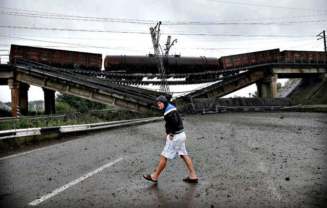 A man walks past a destroyed railroad bridge which fell over a main road leading to the eastern Ukrainian city of Donetsk, near the village of Novobakhmutivka, north of Donetsk July 7, 2014. Ukraine's richest man pleaded with the government on Monday not to bomb Donetsk, a city of a million people where hundreds of heavily armed pro-Russian rebels have vowed to make a stand after losing control of their bastion in the town of Slaviansk. (Photo by Maxim Zmeyev/Reuters)