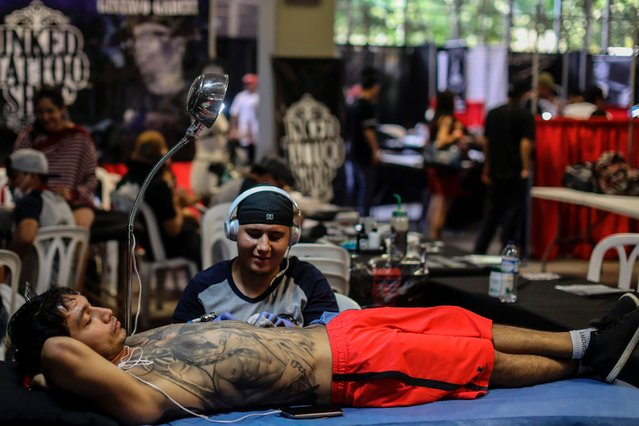A man works in a tattoo during the 8th Expotattoo Colombia Fair in Medellin, Antioquia department, on July 14, 2017. (Photo by Joaquin Sarmiento/AFP Photo)