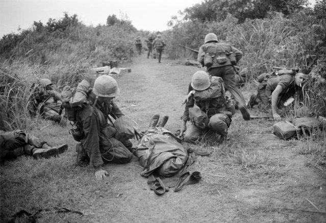 A U.S. Marine wipes tears from his face as he kneels beside a body wrapped in a poncho during a firefight near the demilitarized zone between North and South Vietnam, Sept. 18, 1966