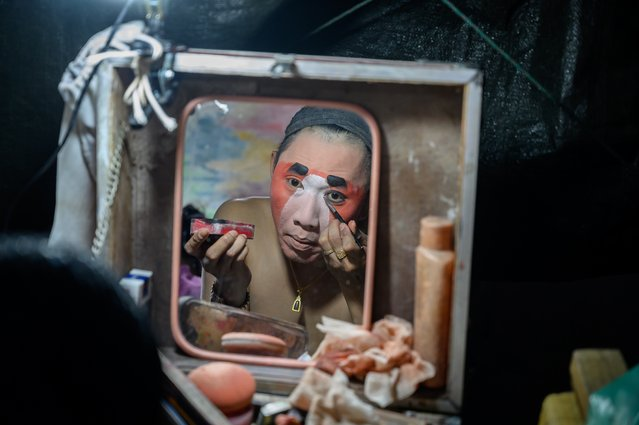 This photograph taken on December 28, 2019 shows a reflection of an actor applying makeup before a Chinese opera performance by Thailand's Sai Bo Hong troupe on a makeshift stage at a street festival in Bangkok. An ancient world of swords, warriors and folklore roars to life on the darkened street, offering a momentary escape from the modern-day bustle of Bangkok's unstoppable development. For centuries, troupes like the Sai Bo Hong Chinese opera have performed throughout Thailand, where 14 percent of the population are ethnic Chinese. (Photo by Mladen Antonov/AFP Photo)