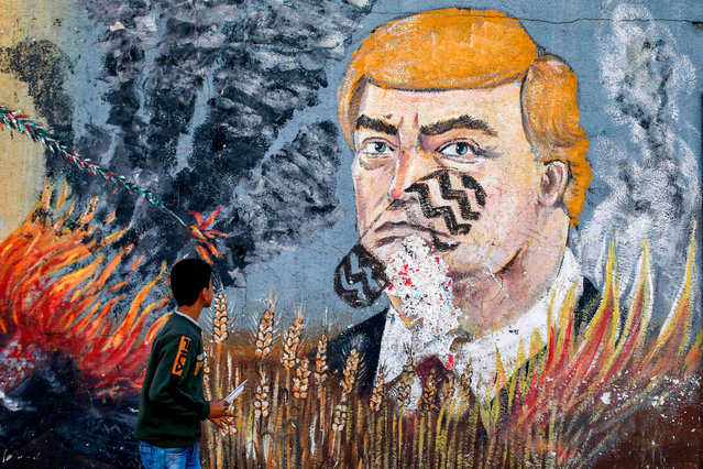 A boy looks at a graffiti mural depicting US President Donald Trump with shoe print on his face, in Gaza City on on December 19, 2019. (Photo by Mohammed Abed/AFP Photo)