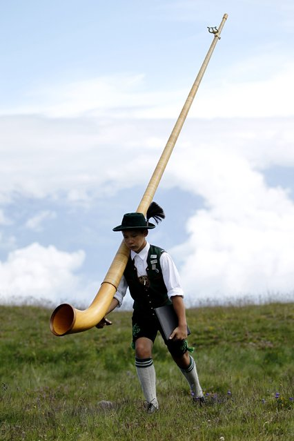 A young Alphorn blower carries his Alphorn before performing an ensemble piece on the last day of the International Alphorn Festival on Lac de Tracouet near the village of Nendaz, July 27, 2014. About 150 alphorn blowers took part in the contest this year. (Photo by Pierre Albouy/Reuters)