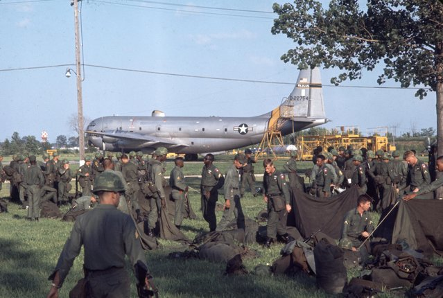 View of US National Guard troops as they sort equipment in a field near a Lockheed C-130 Hercules transport plane, Detroit, Michigan, July 25, 1967. The troops had been sent to Detroit by President Lyndon Johnson during ongoing rioting in the city. (Photo by Lee Balterman/The LIFE Picture Collection/Getty Images)