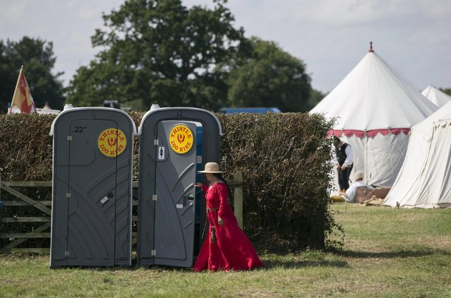 A historical re-enactor uses a portable toilet in a living history camp during an anniversary event for the Battle of Bosworth near Market Bosworth in central Britain August 22, 2015. (Photo by Neil Hall/Reuters)