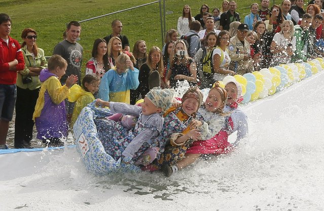 "Children fall as they slide down on a float along a chute to cross a pool of water and foam during the ""Letniy Gornoluzhnik"" (Summer mountain puddle rider) festival at the Bobroviy Log Fun Park near the Siberian city of Krasnoyarsk, Russia, August 23, 2015. The annual competition marks the end of the summer season at the Siberian ski, rest and entertainment resort. (Photo by Ilya Naymushin/Reuters)"