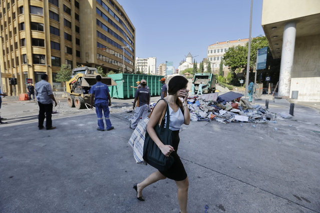 A woman covers her nose as she passes by waste management workers as they collect a pile of garbage near the government building a day after a violent protests against the ongoing trash crisis, in downtown Beirut, Lebanon, Monday, August 24, 2015. (Photo by Hassan Ammar/AP Photo)