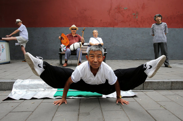 A man performs a split as he practices Kung Fu at Beihai Park in Beijing, China August 20, 2017. (Photo by Reuters/China Stringer Network)