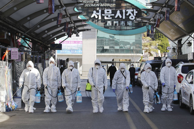 Workers wearing protective gears spray disinfectant as a precaution against the COVID-19 at a local market in Daegu, South Korea, Sunday, February 23, 2020. (Photo by Im Hwa-young/Yonhap via AP Photo)