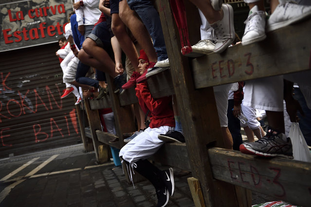 A reveler waits on the barrier of the Estafeta corner the star of the seventh running of the bull with Nunez del Cubillo's fighting bulls, at the San Fermin Festival, in Pamplona, northern Spain, Wednesday, July 13, 2016. Revelers from around the world flock to Pamplona every year to take part in the eight days of the running of the bulls. (Photo by Alvaro Barrientos/AP Photo)
