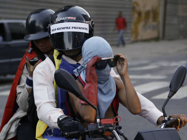 Anti-government protesters ride alongside a march honoring people killed during months of deadly demonstrations against Venezuelan President Nicolas Maduro in Caracas, Venezuela, Wednesday, August 30, 2017. A new United Nations report chronicles swelling violence by Venezuelan security forces over four months this year, appealing to the main U.N.-backed human rights body to address the matter. (Photo by Ricardo Mazalan/AP Photo)