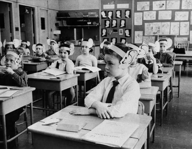 Wearing oversized paper ears, first graders in Baldwin, N.Y., listen attentively during a lesson in phonetics, March 17, 1961. The big ears emphasize the need to listen. (Photo by AP Photo)