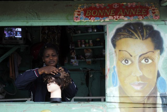 A woman preparing a wig at her hair salon at a shanty town in Abidjan. While reliable Africa-wide figures are hard to come by, market research firm Euromonitor International estimates $1.1 billion of shampoos, relaxers and hair lotions were sold in South Africa, Nigeria and Cameroon alone last year. (Photo by Luc Gnago/Reuters)