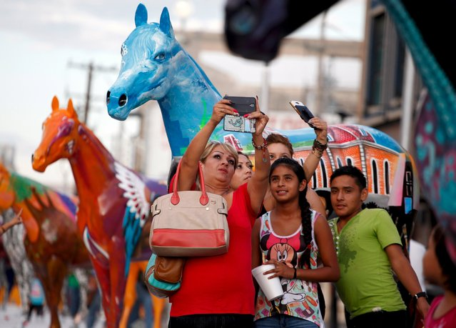 A family takes a selfie in front of sculptures of fiberglass horses in downtown Ciudad Juarez, Mexico, August 25, 2015. (Photo by Jose Luis Gonzalez/Reuters)
