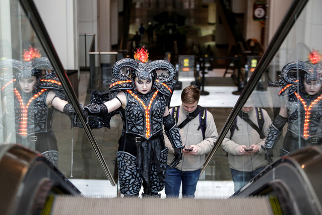 """Emma Randall, dressed as Balrog from """"The Lord of the Rings"""", and boyfriend Connor Sauby, ascend an escalator as a small group of cosplayers gather at the Washington State Convention Center for what would have been the 2020 Emerald City Comic Con, an event organizers said drew 98,000 fans over four days last year, and will be postponed to August due to the coronavirus (COVID-19) outbreak, in Seattle, Washington, U.S. March 14, 2020. (Photo by Jason Redmond/Reuters)"""