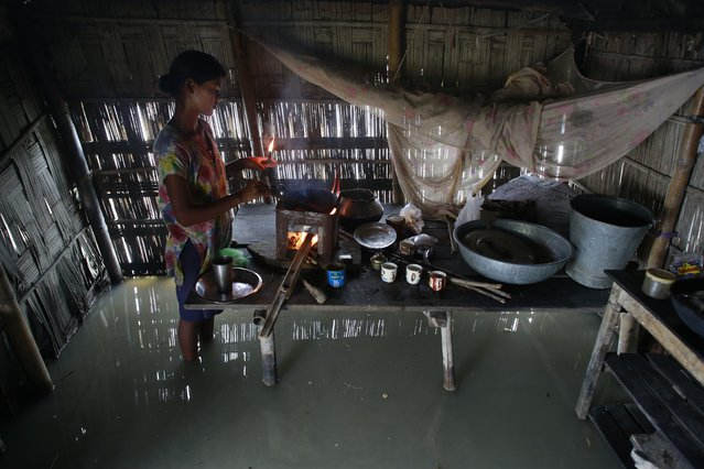 Dupura Akhtar cooks inside her flood-affected house in Ashigarh village, about 70 kilometers (44 miles) east of Gauhati, India, Thursday, August 19, 2014. Heavy rainfall for the past few days has affected several districts of Assam state, flooding dozens of villages and displacing thousands. (Photo by Anupam Nath/AP Photo)