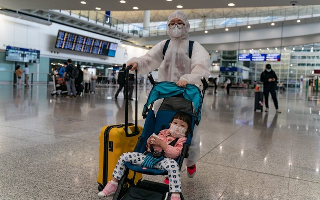 Travellers wearing protective equipment, as a precautionary measure against the COVID-19 coronavirus, enter the arrival hall at the Hong Kong International Airport on March 17, 2020 in Hong Kong, China. Government announced that travellers arriving in Hong Kong from any foreign country from Thursday will be put under 14-day home quarantine or medical surveillance as a red travel alert is issued to cover all overseas nations as part of the emergency response to the coronavirus pandemic. (Photo by Anthony Kwan/Getty Images)