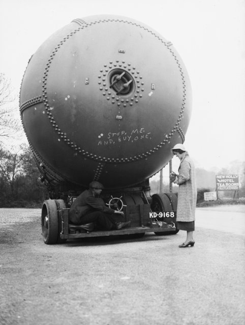 A photographer tries to take a picture of a fifty tonne accumulator which is being transported from Annan in Scotland to Uttoxeter, 9th May 1936.  (Photo by Nick Yapp/Fox Photos)
