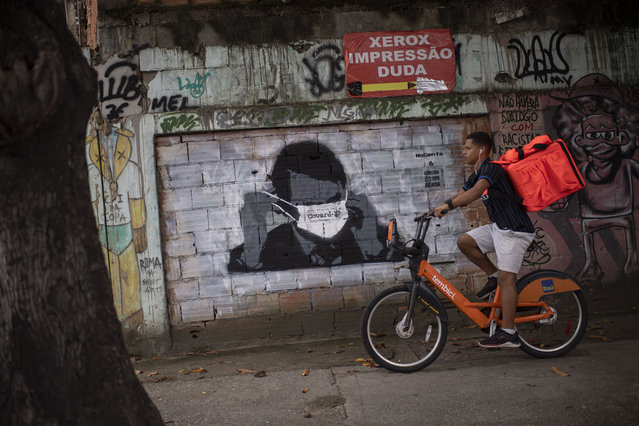 A graffiti of Brazilian President Jair Bolsonaro wearing a face mask is seen on a wall while a delivery man rides a bike in downtown Rio de Janeiro, Brazil, on March 24, 2020 during the coronavirus COVID-19 pandemic. The Rio de Janeiro state government is requesting people not to go to the beach or any other public areas as a measure to contain the coronavirus pandemic. (Photo by Mauro Pimentel/AFP Photo)