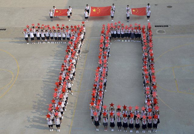 """Students form the figure """"70"""" as they pose with Chinese national flags and red stars during a event to mark the 70th anniversary of the Victory of Chinese People's War of Resistance Against Japanese Aggression and the World Anti-Fascist War, at a primary school in Handan, Hebei province, China, August 31, 2015. China will mark the 70th anniversary of the end of World War Two with a massive military parade this Thursday, with some 12,000 soldiers marching through Beijing's central Tiananmen Square. (Photo by Reuters/China Daily)"""