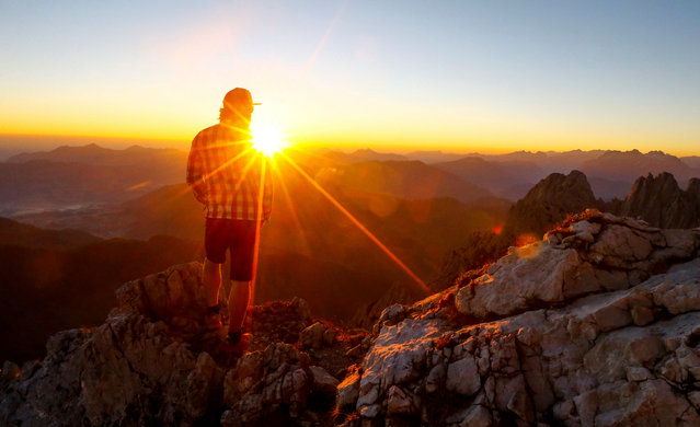 A man watches the sunrise from the peak of the Kaiser Mountains on a summer day in Ellmau, Austria June 24, 2016. (Photo by Dominic Ebenbichler/Reuters)