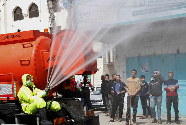 In this March 27, 2020, photo, residents watch workers wearing protective gear spray disinfectant as a precaution against the coronavirus, at the main road of closed market of Shijaiyah neighborhood in Gaza City. Gaza municipality closed all the weekly Friday markets in Gaza starting from today. (Photo by Adel Hana/AP Photo)