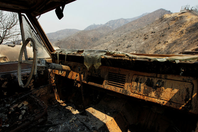 The burned out landscape is seen through the cab of a vehicle at the site of a destroyed house after the Soberanes Fire burned through the Palo Colorado area, north of Big Sur, California, July 31, 2016. (Photo by Michael Fiala/Reuters)