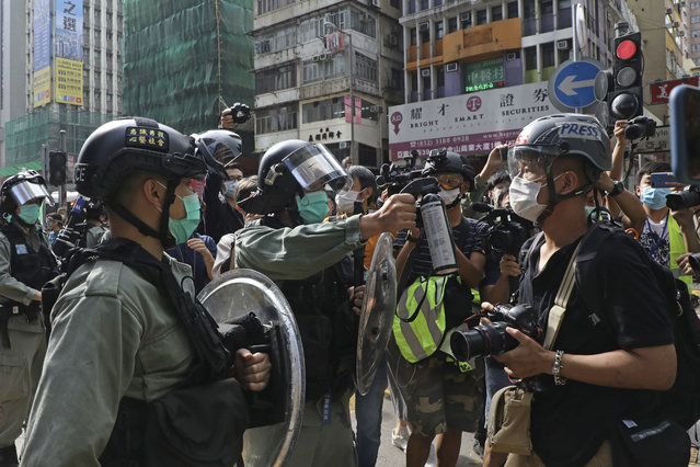 A riot police points the pepper spray to journalists as pro-democracy activists gather outside a shopping mall during the Labor Day in Hong Kong, Friday, May 1, 2020 amid an outbreak of the new coronavirus. May Day usually brings rallies and celebrations rallies marking international Labor Day. This year it's a bitter reminder of how much has been lost for the millions left idle or thrown out of work thanks to the coronavirus pandemic. (Photo by Kin Cheung/AP Photo)
