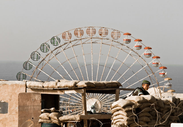 Don't play with war: I was captivated by the scenery before I got my camera out of my bag. In the foreground a soldier in his bunker and in the background a Ferris wheel that looked like it had been shot at. The contrasting dualism in the image struck me before I took the picture. Square/round, adult world/child world, war/peace. Unfortunately I was arrested since I was not allowed to take photos of the military, but I managed to show them a cropped version on my camera screen, displaying only the Ferris wheel. Photo taken in Beirut, Lebanon. (Photo by Janus Langhorn/National Geographic Photo Contest