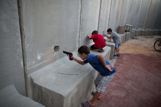Israeli children hold toy guns as they pretend to play war games next to newly built protection cement walls around a kindergarten in the center of Kibbutz Nahal Oz located near the border with Gaza Strip on September 9, 2014. Since the ceasefire between Israel and Hamas following fifty days of fight most of Israeli residents leaving near the Gaza Border hace returned to their homes with high army alert and new measures to protect them. (Photo by Menahem Kahana/AFP Photo)