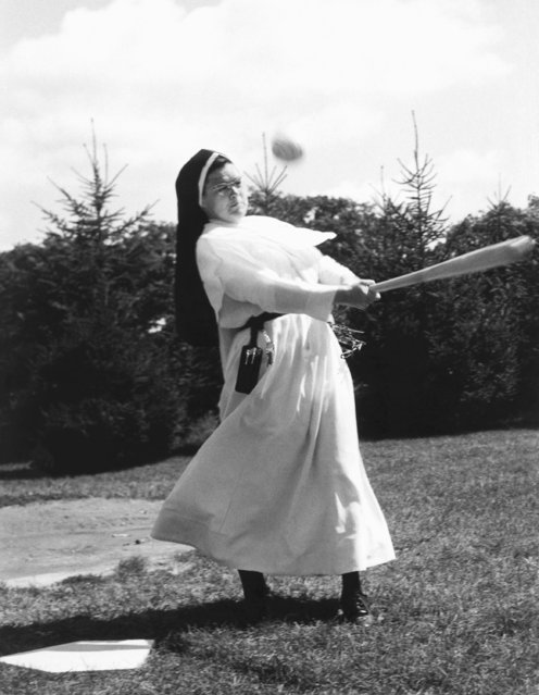 Sister Jean Raymond swings hard but hits a foul ball while playing soft ball with a group of nuns and priests at a pre-school picnic held at St. Monica Seminar near Oconomowoc, Wisconsin, September 9, 1966. Sister Raymond, principal of Holy Name School in Racine, Wisconsin, met with other Sisters from several southeastern Wisconsin communities at the seminar and were guests of Augustinian Fathers and seminarians of St. Monica's. (Photo by AP Photo)