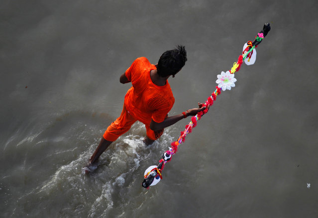A Kanwariya or a devotee of the Hindu Lord Shiva arrives to fill his pots with holy water from the river Ganga, for the betterment of his family and the society, in Allahabad, India, August 4, 2016. (Photo by Jitendra Prakash/Reuters)