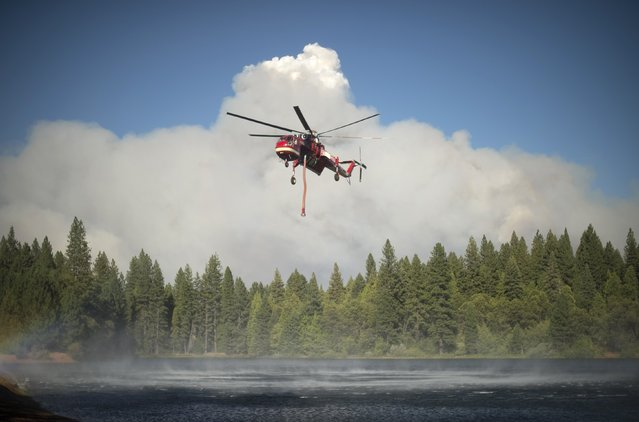 A helicopter draws water from a lake as smoke rises from the King Fire in Pollock Pines, California September 17, 2014. (Photo by Noah Berger/Reuters)