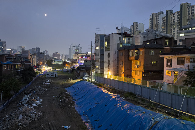 Full moon is seen over an old train track site in Hongdae area on July 30, 2015 in Seoul, South Korea. The old train track was the part of Gyeongui Line which connects Seoul and Incheon, and the site will be transformed to a public park by local government. The view is from Wawoo bridge. The Hongdae area is a region around Hongik University in Seoul, South Korea. Hongdae is an abbreviation of 'Hong'ik 'Dae'hakyo, Hongik University. (Photo by Shin Woong-jae/The Washington Post)